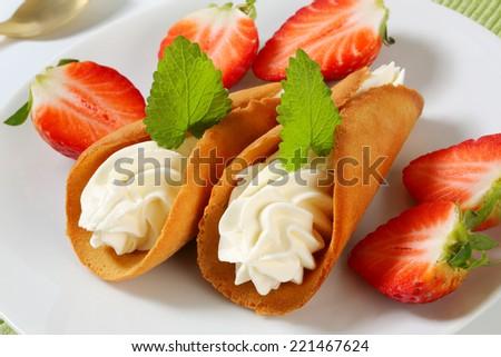 Czech cream-filled gingerbread cookies (Stramberk ears) with fresh strawberries - stock photo