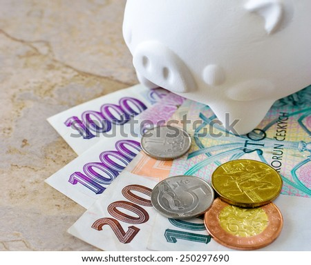 Czech crown banknotes and coins with piggy bank - cash as savings - economy and finance - stock photo