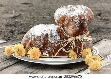 Czech Easter - baked lamb with powdered sugar and dandelions on old wood desk - stock photo