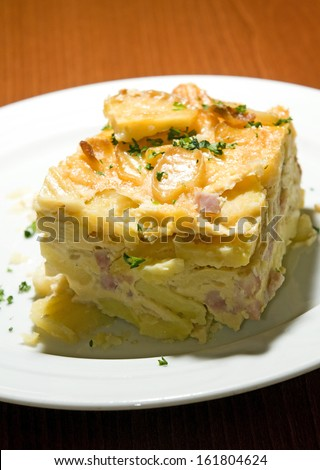 Czech Republic food specialty baked sliced potato with smoked bacon bits photographed in Prague Castle authentic typical delicacy  - stock photo