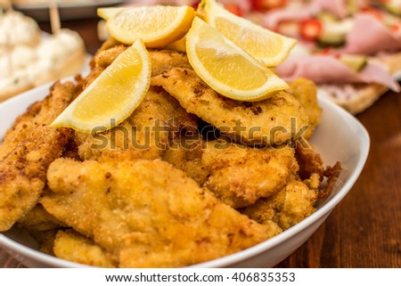 Czech traditional schnitzel with lemon on wood table