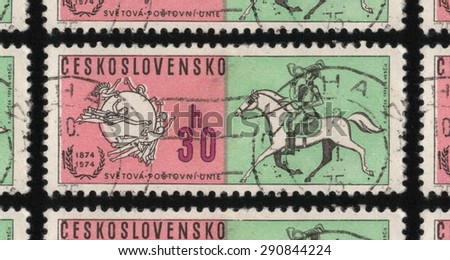 "CZECHOSLOVAKIA - CIRCA 1974: A postage stamp printed in Czechoslovakia from the ""The 100th Anniversary of the Universal Postal Union"" issue, shows horse and rider and Universal Postal Union symbol."