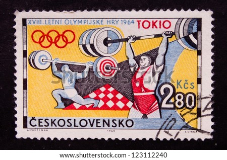 CZECHOSLOVAKIA- CIRCA 1964: A stamp printed in Czechoslovakia shows an Olympic sportsman weightier in red clothing, circa 1964.