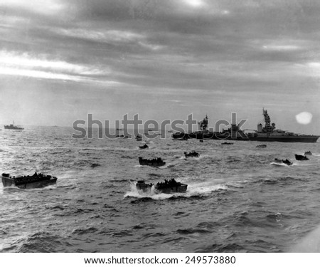 D-Day landing craft head for Omaha beach during the Normandy invasion on June 6, 1944. in right background is the cruiser USS Augusta, flagship of the Western Naval Task Force. - stock photo
