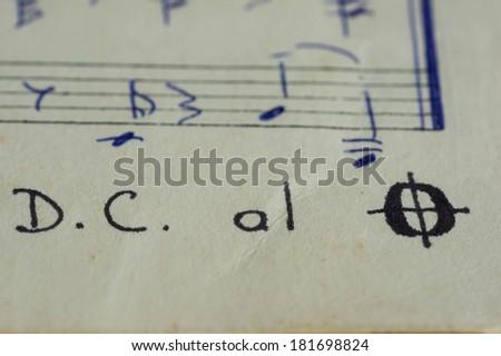 Da Capo al Fine in a music book with hand-written notes close up - stock photo