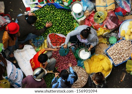 DA LAT, VIET NAM- FEB 8: Crowded atmosphere at outdoor farmers market, people buy vegetable, the colorful overview of fresh vegetable with people at open air market in Dalat, VietNam on Feb 8, 2013 - stock photo