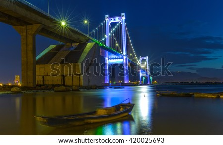 Da Nang, Vietnam - June 25th, 2015: Beauty Thuan Phuoc Bridge architecture inside marina with glowing lights rays shining down river carried reliability in Da Nang, Vietnam