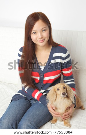 Dachshund and young Asian teens - stock photo