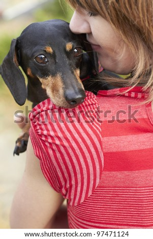 Dachshund dog looking over shoulder while owner gives a loving hug - stock photo
