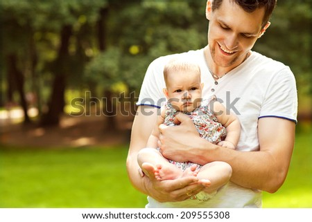 dad and baby daughter playing in the park in lovedad and baby daughter playing in the park in love - stock photo