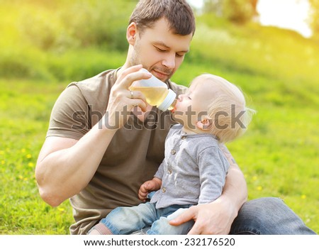 Dad and baby together, father feeding baby outdoors summer - stock photo