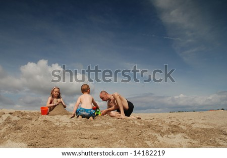 Dad and children having fun on the beach