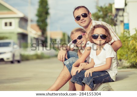 Dad and children playing near a house at the day time. Concept of friendly family. - stock photo