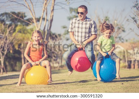 Dad and children playing on the lawn in front of house at the day time - stock photo