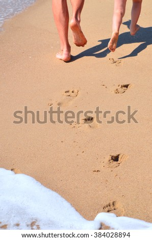 Dad and daughter are running on the beach.  Only  legs and footprints in the sand are visible - stock photo
