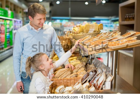 Dad and daughter at bakery - stock photo