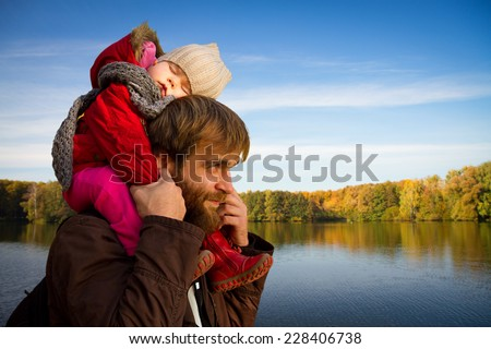 Dad and daughter. daughter fell asleep on his neck with his father in autumn park - stock photo