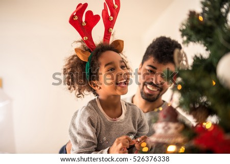 People Decorating A Christmas Tree african family decorating christmas tree stock images, royalty