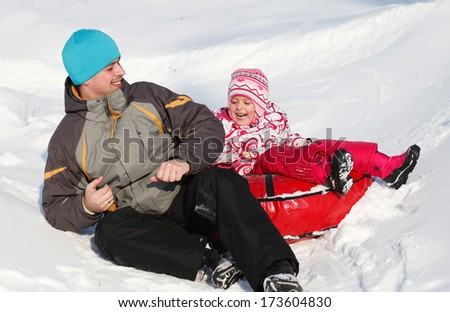 Dad and daughter having fun in snow  - stock photo