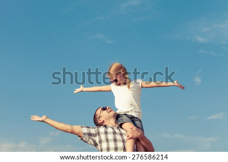 Dad and daughter in sunglasses playing near a house at the day time. Concept of friendly family.