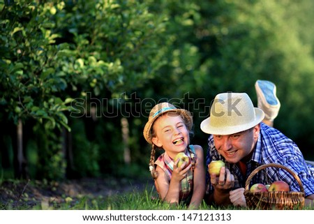 Dad and daughter laughing in a fruit orchard
