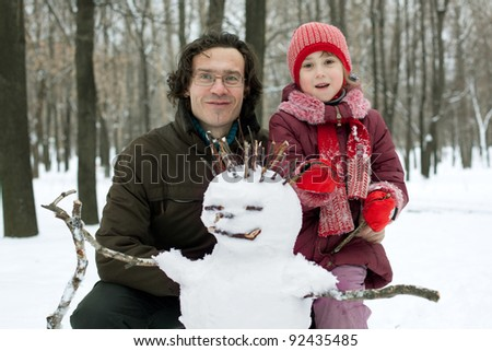 Dad and daughter next to the snowman in winter forest - stock photo