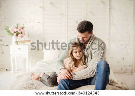 Dad and daughter playing and laughing in bed, happy family