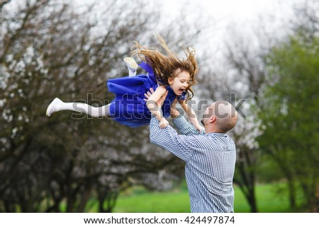 Dad and daughter playing in the park. - stock photo