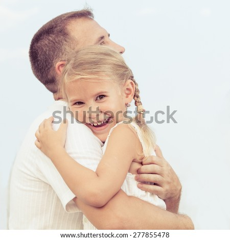 Dad and daughter  playing near a house at the day time. Concept of friendly family.