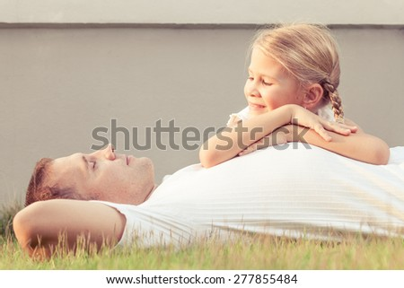 Dad and daughter  playing near a house at the day time. Concept of friendly family. - stock photo