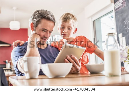 Dad and his eight year old son using a digital tablet while having breakfast in the kitchen. They are wearing casual clothes