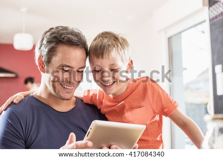 Dad and his eight year old son using a digital tablet while having breakfast in the kitchen. They are wearing casual clothes - stock photo