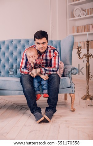 Dad and his son sitting on blue sofa modern, minimalist. light interior indoors. hugging with toddler. Child making funny facial expressions. family love concept. having fun