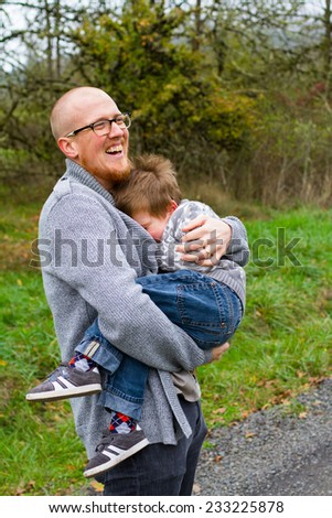 Dad and his son together in a lifestyle family portrait outdoors in the Fall. - stock photo