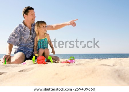 Dad and little daughter playing on the beach - stock photo