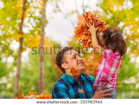 Dad and little daughter with pile of maple leaves - stock photo