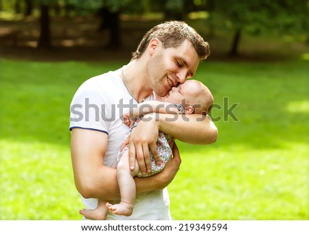 dad and newborn daughter playing in the park in love - stock photo