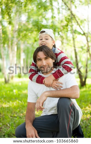 Dad and son at the park during the summer - stock photo