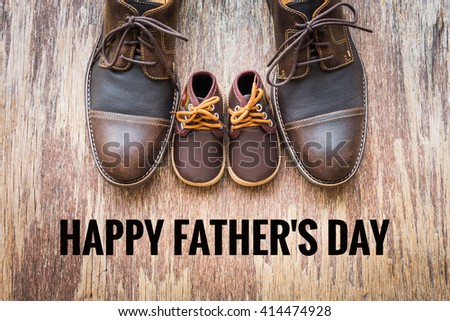 Dad and son brown shoes on rustic wooden background with happy father's day wording - stock photo