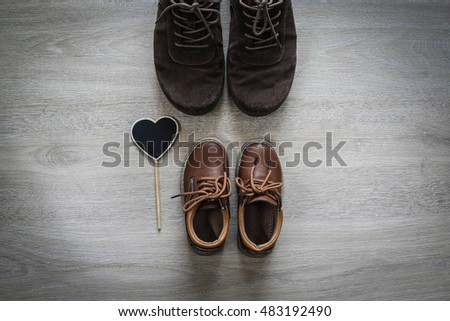 Dad and son brown shoes with red heart on wooden background,fathers day