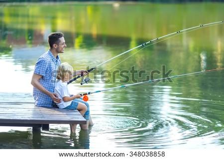 Dad and son fishing at lake - stock photo
