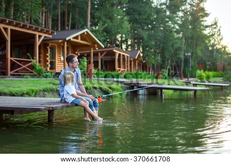 Dad and son fishing on lake - stock photo