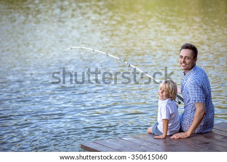 Dad and son fishing outdoors