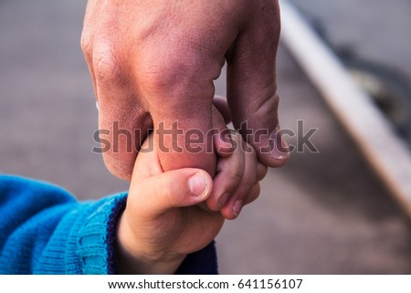 dad and son holding hands