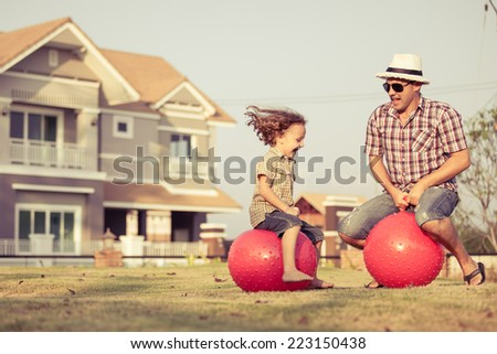 Dad and son jumping on inflatable balls on the lawn in front of house at the day time - stock photo