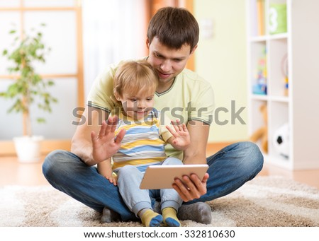 dad and son kid playing with tablet computer indoors - stock photo