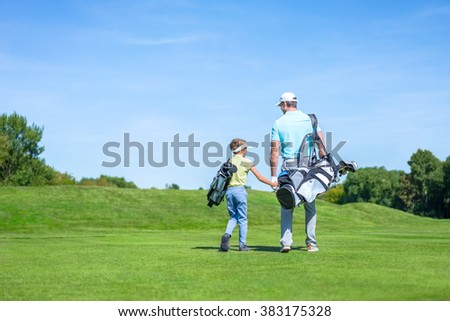 Dad and son on golf course - stock photo