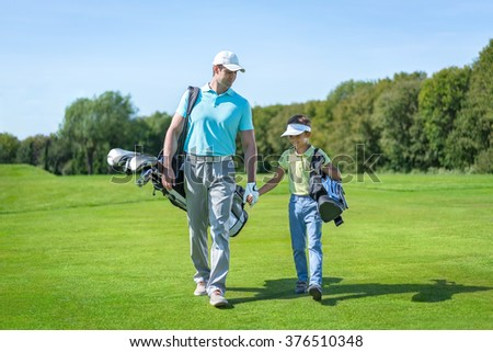 Dad and son on golf lawn - stock photo