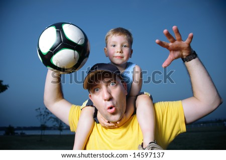 Dad and son playing football outdoors - stock photo