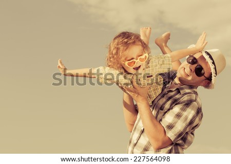 Dad and son playing near a house at the day time - stock photo